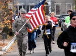 a contestant in military garb carries an American flag as he runs up Front St. heading west toward Washington Ave. in the Schenectady Stockade - Stockade-athon 2010 - 07Nov2010