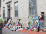 an artist proudly presents her work on Front St.