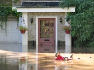 a child's red wagon floats in post-Irene flood waters past the front door of No. Cucumber Alley, Schenectady NY Stockade, 29Aug2011