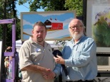 Val Robert being given the 1st Place Ribbon at the 2014 Stockade Outdoor Art Show by Bill Buell on behalf of the Gazette